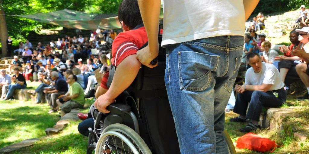 Qui sommes-nous. Photographie d'une personne en fauteuil roulant, accompagnée par une autre personne lors de l'événement Vent dans les Branches